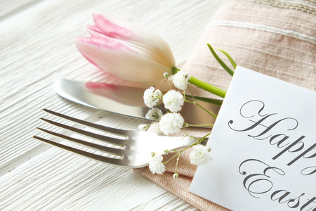 Easter table setting composition with fork & knife silverware, pink tulip tied with pink ribbon on white wooden texture table background. Happy easter greeting card. Close up, top view, copy space. Stock Photo