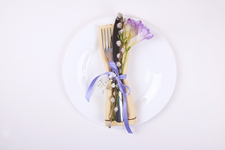 Wedding table setting composition with fork & knife silverware, purple freesia flower & pussy willow, tied ribbon on white table background. Happy easter greeting card. Top view, close up, copy space. Banque d'images - 120536740