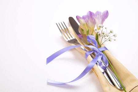 Wedding table setting composition with fork & knife silverware, purple freesia flower & gypsophila, tied ribbon on white table background. Happy easter greeting card. Top view, close up, copy space.