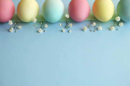Beautiful easter table setting composition. A row of pastel color eggs, pink, blue and yellow, white gypsophila wildflower flower on blue background. Happy Easter greeting card. Top view, copy space.