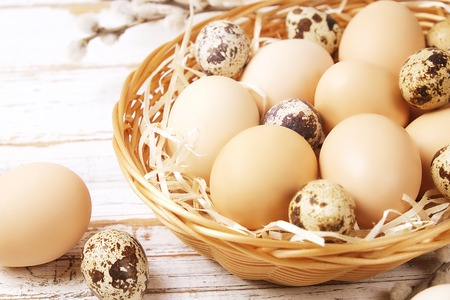 Beautiful easter table composition. Unpainted organic quail & chicken eggs in wicker basket, decorative pussy willow branches on wood textured background. Greeting card template. Close up, top view.