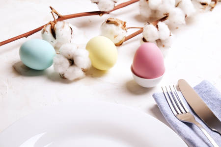 Beautiful easter table setting composition. Pastel color eggs in egg cup, pink, blue & yellow on table top. Blank template for Easter greeting card. Top view, festive background, flat lay, copy space.