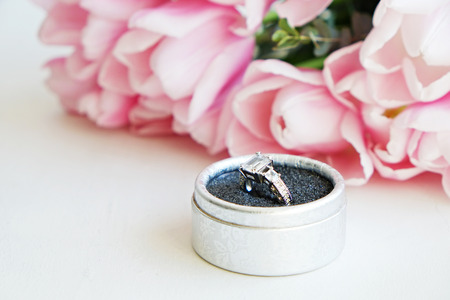 Macro shot of expensive white gold diamond ring and beautiful tender pink tulips. Top view composition with engagement ring and flower petals. Feminine wedding background with copy space for text.