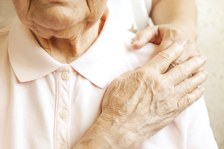 Mature female in elderly care facility gets help from hospital personnel nurse. Senior woman, aged wrinkled skin & hands of her care giver. Grand mother everyday life. Background, copy space, close up Stok Fotoğraf