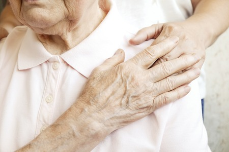 Mature female in elderly care facility gets help from hospital personnel nurse. Senior woman, aged wrinkled skin & hands of her care giver. Grand mother everyday life. Background, copy space, close up 스톡 콘텐츠
