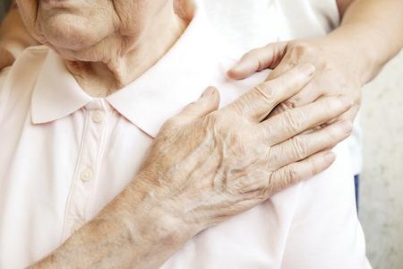 Rijpe vrouw in bejaardentehuis krijgt hulp van verpleegster van ziekenhuispersoneel. Hogere vrouw, verouderde gerimpelde huid & handen van haar verzorger. Grootmoeder dagelijks leven. Achtergrond, kopieer ruimte, close-up Stockfoto