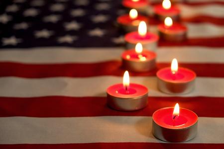 Bougies de deuil brûlant sur fond de drapeau national américain des États-Unis. Week-end commémoratif, journée des anciens combattants patriotes, Journée nationale du service et du souvenir du 11 septembre. Concept de moment de silence. Gros plan, copiez l'espace.