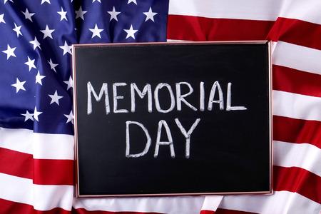 阵亡将士纪念日周末的文字写在带有美国国旗的黑色木制黑板上。美国星条旗爱国者老兵纪念象征。背景,关闭,复制空间,俯视图。