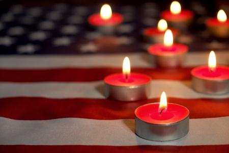 以美国国旗为背景点燃哀悼蜡烛。阵亡将士纪念日、爱国者退伍军人日、9/11国家服务纪念日。默哀时刻的概念。关闭,拷贝空间。