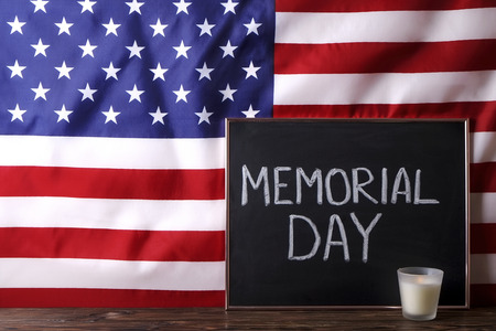 Memorial day weekend text written on wooden black chalkboard, candle w/ USA flag background. United States of America stars & stripes patriot veteran remembrance symbol. Close up, copy space, top view