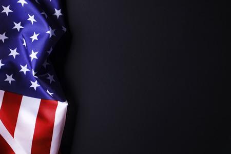 Patriotische Komposition mit gekräuselter amerikanischer Flagge auf schwarzem Hintergrund. Vereinigte Staaten von Amerika Stars & Stripes-Symbol mit Kopie für Text. 4. Juli Konzept zum Unabhängigkeitstag. Hintergrund, Nahaufnahme