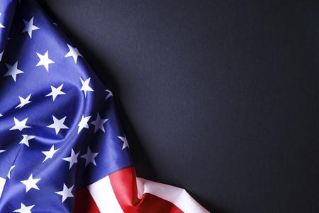 Patriotische Komposition mit gekräuselter amerikanischer Flagge auf schwarzem Hintergrund. Vereinigte Staaten von Amerika Stars & Stripes-Symbol mit Kopie für Text. 4. Juli Konzept zum Unabhängigkeitstag. Hintergrund, Nahaufnahme Standard-Bild
