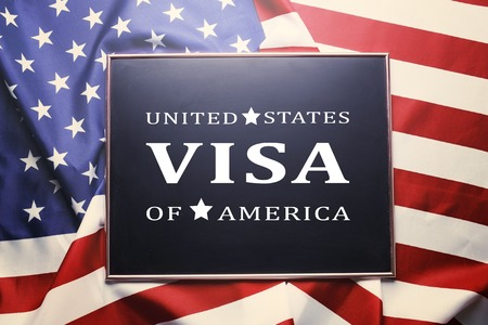 Close up of black chalkboard with UNITED STATES OF AMERICA VISA text written on it. Visa application formalization concept. Ruffled USA American flag background. Top view, copy space.