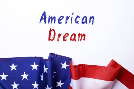 American dream text in blue & red letters on white background with ruffled flag of USA. Martin Luther King Jr. day concept. Close up, copy cpace.