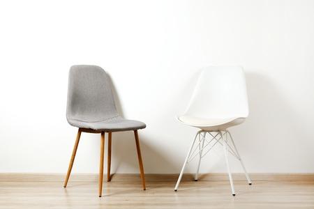 Sedia vuota stile loft su sfondo bianco muro con un sacco di spazio copia per il testo. Posizione di lavoro disponibile, colloquio o concetto di trattative.