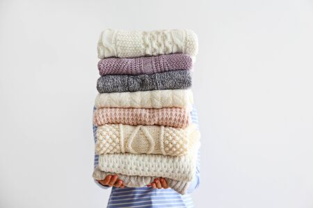 Slim young woman wearing oversized cotton shirt with blue stripes & holding big stack of folded knitted warm pastel color sweaters, easy chic style, different knitting patterns. Background, copy space