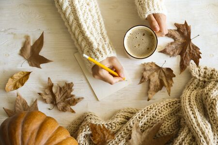 Top view composition with young woman's hands in white sweater, vintage styled cup of coffee and autumn themed decoration, fallen leaves on textured background. Flat lay, copy space.
