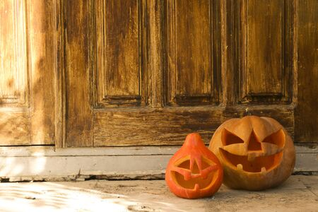 Few orange pumpkins of different size carved into Jack o Lantern on the porch. Background, copy space, close up, top view. All hallows eve Halloween party decoration. Trick or treat concept.
