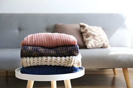 Bunch of knitted pastel color sweaters with different knitting patterns perfectly folded in stack on white coffee table, white brick wall background. Fall winter season knitwear. Close up, copy space