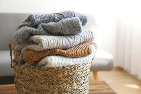 Bunch of stacked knitted pastel color sweaters with different knitting patterns perfectly folded in wicker basket on table, living room background. Fall winter season knitwear. Close up, copy space. Banque d'images