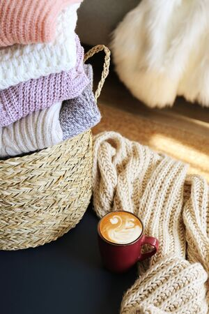 Bunch of stacked knitted pastel color sweaters with different knitting patterns perfectly folded in wicker basket on table, living room background. Fall winter season knitwear. Close up, copy space. Stock Photo