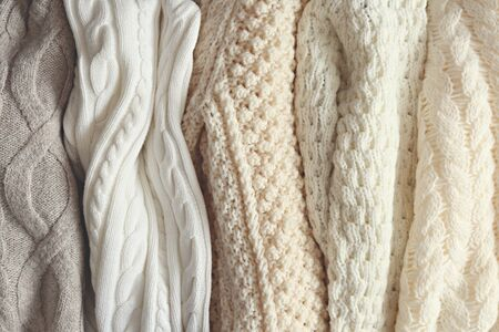 Bunch of knitted warm pastel color sweaters with different vertical knitting patterns hanging in bunch, clearly visible texture. Stylish fall / winter season knitwear clothing. Close up, copy space. Stock Photo