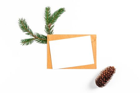 Festive flat lay composition with blank invitation for new year celebration and craft paper envelope. Christmas greeting card template concept. Background, copy space, top view.
