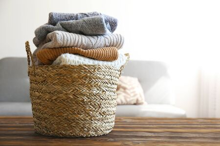 Bunch of stacked knitted pastel color sweaters with different knitting patterns perfectly folded in wicker basket on table, living room background. Fall winter season knitwear. Close up, copy space. Archivio Fotografico