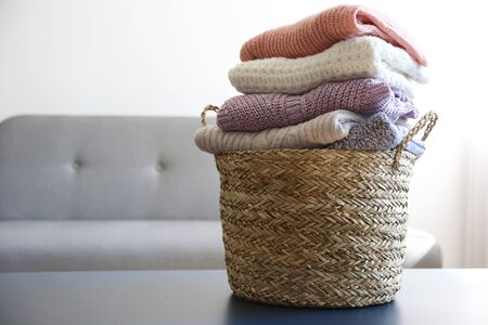 Bunch of stacked knitted pastel color sweaters with different knitting patterns perfectly folded in wicker basket on table, living room background. Fall winter season knitwear. Close up, copy space. Banque d'images - 131749524