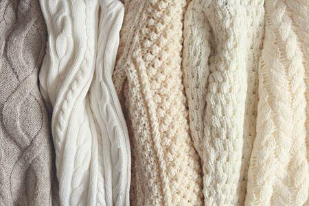 Montón de suéteres de punto de color pastel cálido con diferentes patrones de tejido verticales colgando en un montón, textura claramente visible. Prendas de punto con estilo para la temporada de otoño / invierno. De cerca, copie el espacio.