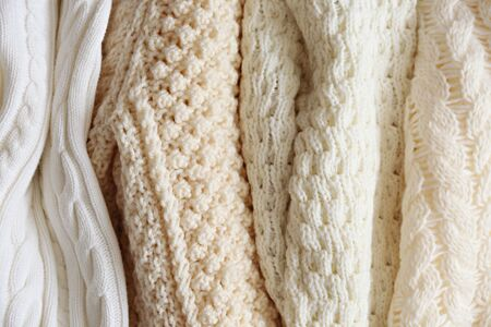 Bunch of knitted warm pastel color sweaters with different vertical knitting patterns hanging in bunch, clearly visible texture. Stylish fall  winter season knitwear clothing. Close up, copy space. 版權商用圖片