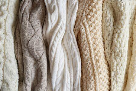 Montón de suéteres de punto de color pastel cálido con diferentes patrones de tejido verticales colgando en un montón, textura claramente visible. Prendas de punto con estilo para la temporada de otoño / invierno. De cerca, copie el espacio. Foto de archivo