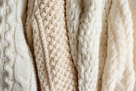 Bunch of knitted warm pastel color sweaters with different vertical knitting patterns hanging in bunch, clearly visible texture. Stylish fall  winter season knitwear clothing. Close up, copy space. Reklamní fotografie