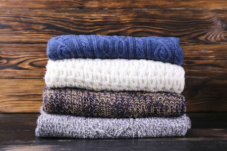 Bunch of knitted pastel color sweaters with different knitting patterns perfectly folded in stack on brown wooden table, wood textured background. Fall winter season knitwear. Close up, copy space.