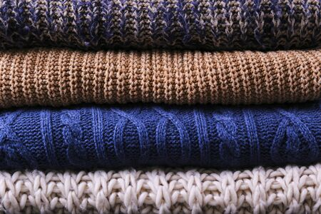 Bunch of knitted warm pastel color sweaters with different knitting patterns folded in stack, clearly visible texture. Stylish fall / winter season knitwear clothing. Close up, copy space for text. Foto de archivo