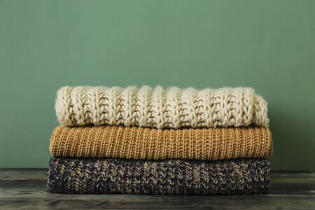 Bunch of knitted pastel color sweaters with different knitting patterns perfectly folded in stack on brown wooden table, green textured background. Fall winter season knitwear. Close up, copy space.