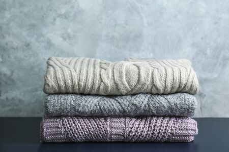 Bande de chandails tricotés de couleur pastel chaude avec différents motifs de tricot pliés en pile sur une table en bois marron, fond de mur de texture grunge. Tricots de saison automne hiver. Gros plan, espace de copie