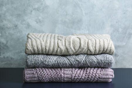 Kilka dzianinowych swetrów w ciepłych pastelowych kolorach z różnymi wzorami dziania złożonymi w stos na brązowym drewnianym stole, grunged tekstura tło ściany. Jesienno-zimowa dzianina. Zamknij, skopiuj miejsce