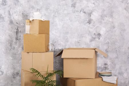 Bunch of blank unsigned moving boxes in new empty apartment. Spacious unfurnished room with unpacked cardboard box stack. Interior background, copy space for text. Stok Fotoğraf