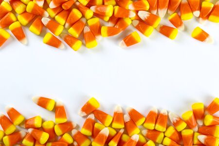 Bunch of candy corn sweets as sybol of Halloween hoiday on textured background with a lot of copy space for text. Flat lay composition for all hallows eve. Top view shot.
