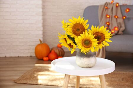 Beautiful yellow sunflowers in vase on white coffee table in the middle of lofty apartment, organic orange pumpkins on wooden floor. Interior with grey sofa, brick wall backgroud. Close up, copy space Foto de archivo