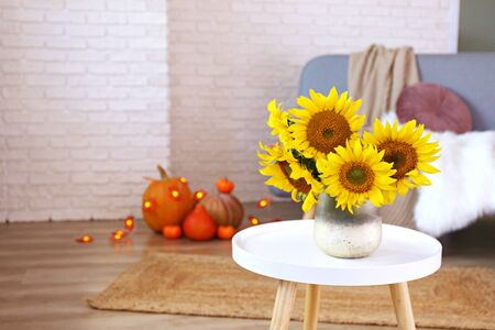 Beautiful yellow sunflowers in vase on white coffee table in the middle of lofty apartment, organic orange pumpkins on wooden floor. Interior with grey sofa, brick wall backgroud. Close up, copy space