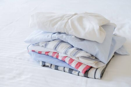 Hotel room with freshly made bed, perfectly clean and ironed sheets, stack of new dry cleaned folded set of clothing in natural sun light. Close up, copy space for text.