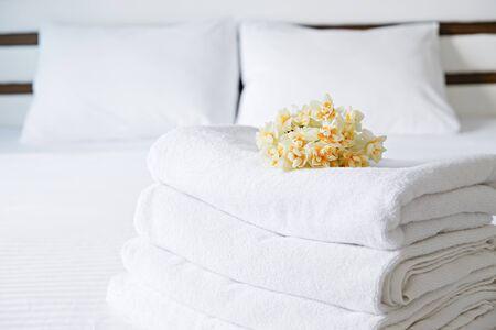 Hotelzimmer mit frisch gemachtem Bett, perfekt sauberer und gebügelter schneeweißer Bettwäsche, Stapel neuer gefalteter Handtücher im natürlichen Sonnenlicht. Nahaufnahme, kopieren Sie Platz für Text.