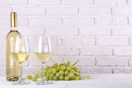 Vintage bottle of white wine without label, two glasses and bunch of grapes on wooden table, lofty white brick wall background. Expensive bottle of chardonnay concept. concept. Copy space.