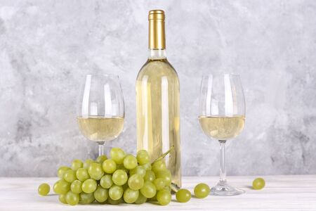 Vintage bottle of white wine without label, two glasses and bunch of grapes on wooden table, lofty grunged concrete wall background. Expensive bottle of chardonnay concept. concept. Copy space,