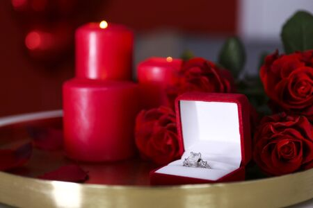 Marry me concept, wedding / engagement ring in open jewelry box with red candles, beautiful roses bouquet. Happy st. valentine's day concept. Close up, copy space, front view