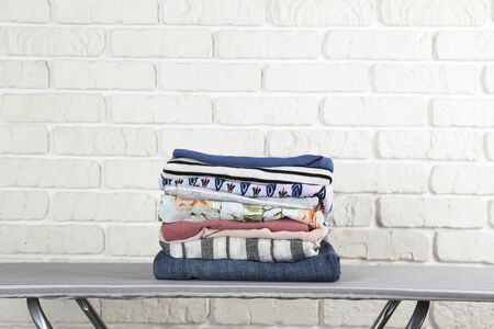 Stack of clean freshly laundered, neatly folded womens clothes on pressboard. Pile of shirts, dresses and sweaters on striped ironing board, concrete wall background. Copy space, close up, top view.