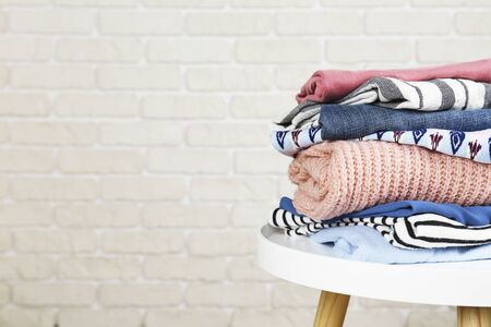 Stack of clean freshly laundered, neatly folded womens clothes on wooden table. Pile of shirts, dresses and sweaters on white board, concrete wall background. Copy space, close up, top view. Stock Photo