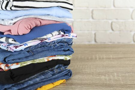 Stack of clean freshly laundered, neatly folded womens clothes on wooden table. Pile of shirts, dresses and sweaters on the board, white brick wall background. Copy space, close up, top view.